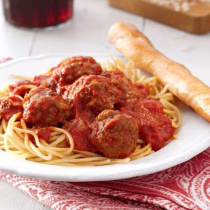 Linguini tossed with marinara over meatballs